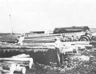 Black and white image of poles in a pile